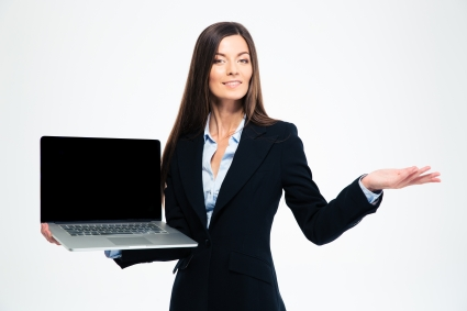Happy businesswoman showing blank laptop screen and holding copyspace on the palm isolated on a white background. Looking at camera
